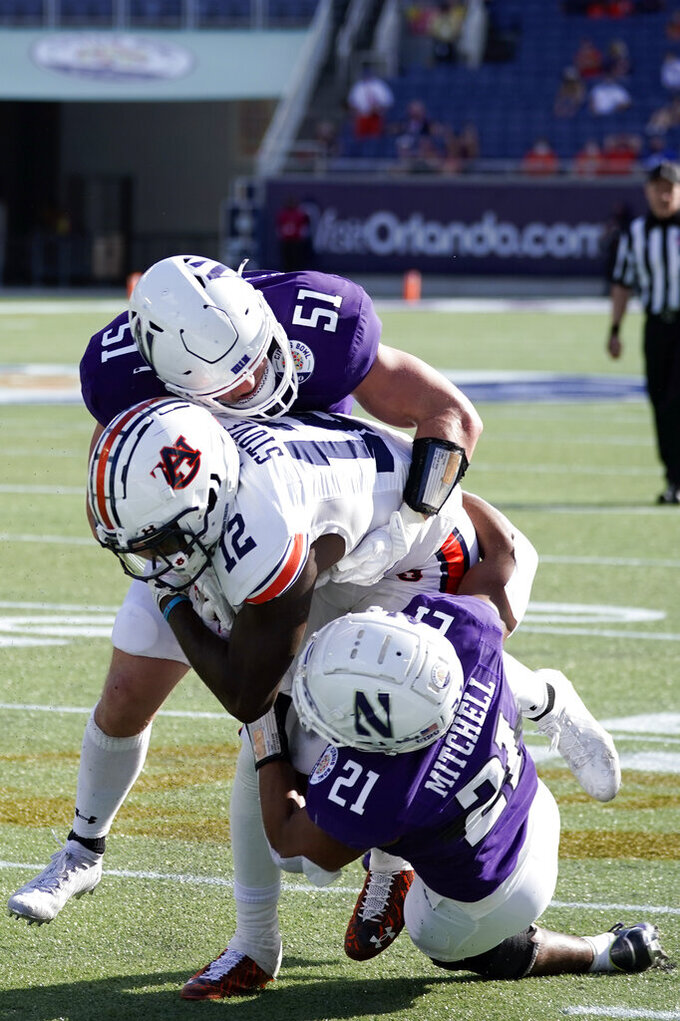 Northwestern linebacker Blake Gallagher (51) and defensive back Cameron Mitchell (21) bring down Auburn wide receiver Eli Stove (12) after a reception during the first half of the Citrus Bowl NCAA college football game, Friday, Jan. 1, 2021, in Orlando, Fla. (AP Photo/John Raoux)