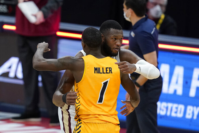 UNC-Greensboro's Isaiah Miller (1) and Florida State's RaiQuan Gray (1) hug following a first-round game in the NCAA men's college basketball tournament at Banker's Life Fieldhouse, Saturday, March 20, 2021, in Indianapolis. Florida State defeated UNC-Greensboro 64-54. (AP Photo/Darron Cummings)