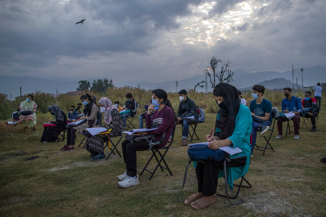 Kashmiri students attend an open-air early morning class inside Eidgah, a ground reserved for Eid prayers, in Srinagar, Indian controlled Kashmir, Friday, July 18, 2020. When months went by without teaching, Muneer Alam, an engineer-turned-math teacher, started the informal community school in the form of an open-air classroom in June. Schools in the disputed region reopened after six months in late February, after a strict lockdown that began in August 2019, when India scrapped the region's semi-autonomous status. In March schools were shut again because of the coronavirus pandemic. (AP Photo/Dar Yasin)