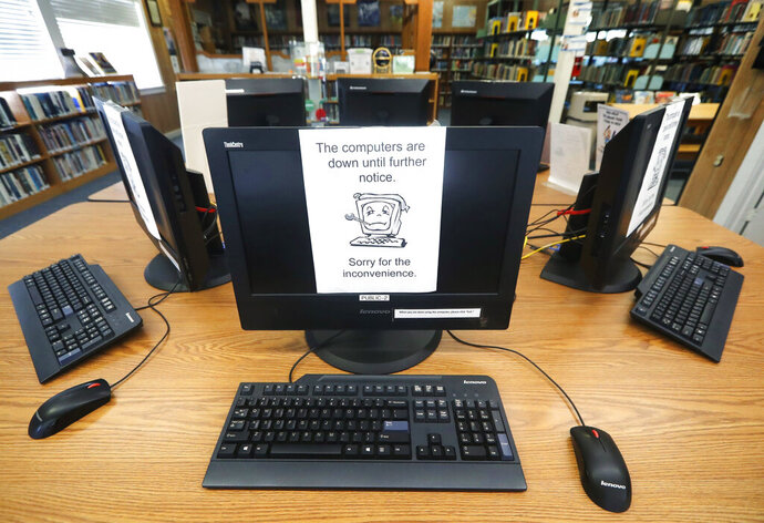 FILE - In this Aug. 22, 2019, file photo, signs on a bank of computers tell visitors that the machines are not working at the public library in Wilmer, Texas. Some cybersecurity professionals are concerned that insurance policies designed to limit the damage of ransomware attacks might actually be encouraging hackers. Twenty-two local governments in Texas were hit in August. (AP Photo/Tony Gutierrez, File)