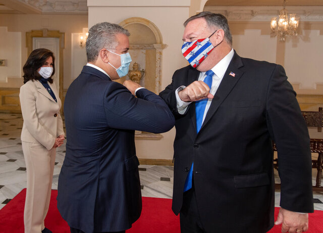In this handout photo released by Colombia's Presidential Press Office, Colombian President Ivan Duque and U.S. Secretary of State Mike Pompeo bump elbows before their meeting at the presidential house in Bogota, Colombia, Saturday, Sept. 19, 2020. Pompeo on Saturday wrapped up a tour of four South American countries — three of them neighbors of Venezuela, whose socialist government is under intense U.S. pressure. (Nicolas Galeano/Colombia's Presidential Press Office via AP)