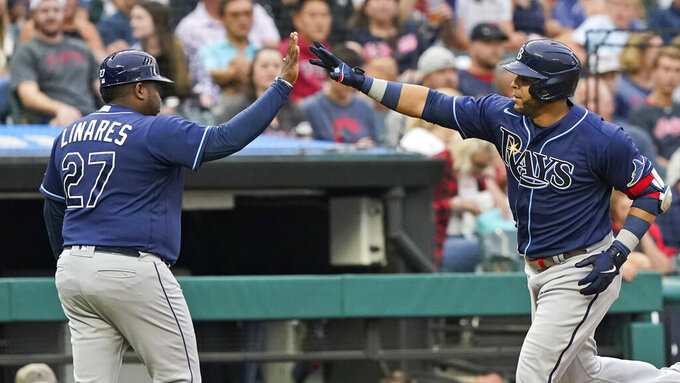 Tampa Bay Rays' Nelson Cruz, right, is congratulated by third base coach Rodney Linares after Cruz hit a solo home run during the third inning of a baseball game Friday, July 23, 2021, in Cleveland. (AP Photo/Tony Dejak)