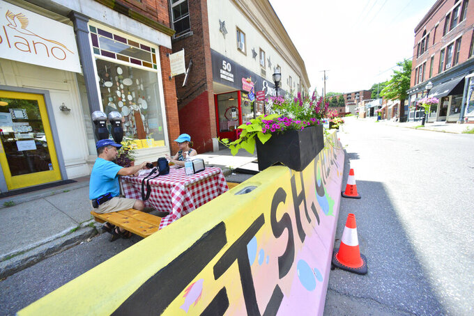 Lori and John Basile enjoy a meal from Elliot Street Fish and Chips in one of the dining areas that was created in a parking spot in Brattleboro Monday, July 20, 2020. The outdoor seating was created to help with social distance during the COVID-19 pandemic. (Kristopher Radder, Brattleboro Reformer via AP)