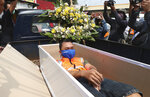 A man lays inside a mock coffin as punishment for violating city regulations requiring people to wear face masks in public places as a precaution against the new coronavirus outbreak in Jakarta, Indonesia, Thursday, Sept. 3, 2020. (AP Photo/Achmad Ibrahim)