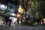 In this Tuesday, Jan. 7, 2020, photo, Taiwanese residents pass near stores with a campaign billboard showing Taiwan President Tsai Ing-wen in Taipei, Taiwan. Taiwan's ruling party is crying foul over alleged Chinese attempts to sway the self-governing island's presidential election on Saturday. The Democratic Progressive Party, known as the DPP, rushed through a law banning