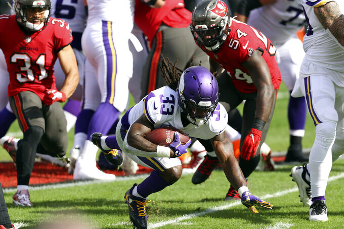 Minnesota Vikings running back Dalvin Cook (33) dives for yardage after getting past Tampa Bay Buccaneers strong safety Antoine Winfield Jr. (31) and inside linebacker Lavonte David (54) during the first half of an NFL football game Sunday, Dec. 13, 2020, in Tampa, Fla. (AP Photo/Mark LoMoglio)