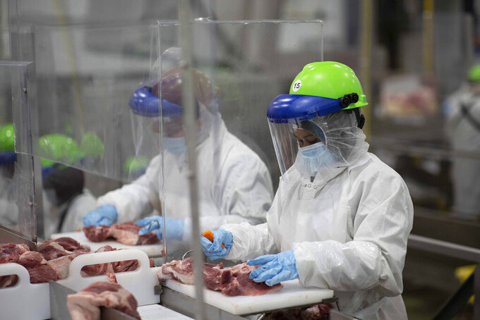 This May 20, 2020, photo provided by Smithfield Foods shows some of the measures the company says it has taken to limit the spread of the coronavirus inside its plants. Workers inside its Sioux Falls, South Dakota, pork processing plant wear protective gear and are separated by plastic partitions as they carve up meat.(Photo courtesy Smithfield Foods via AP)
