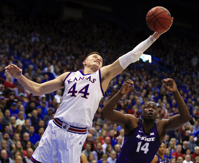 Kansas forward Mitch Lightfoot (44) rebounds over Kansas State forward Makol Mawien (14) during the second half of an NCAA college basketball game in Lawrence, Kan., Monday, Feb. 25, 2019. (AP Photo/Orlin Wagner)
