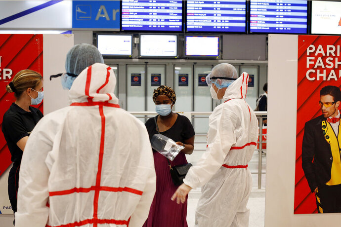 A passenger arrives to be tested with the COVID-19 test, at the Roissy Charles de Gaulle airport, outside Paris, Saturday, Aug. 1, 2020. Travelers entering France from 16 countries where the coronavirus is circulating widely are having to undergo virus tests upon arrival at French airports and ports.(AP Photo/Thibault Camus)