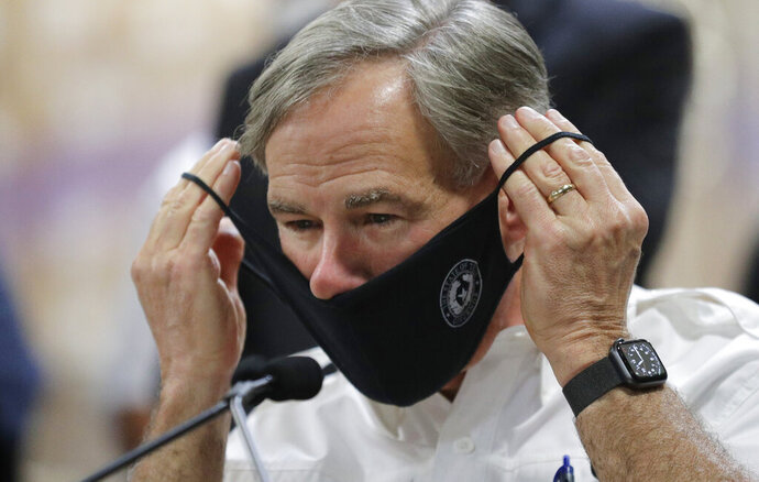 Texas Gov. Greg Abbott wears a face mask during a visit to a Texas Division of Emergency Management Warehouse filled with Personal Protective Equipment, Tuesday, Aug. 4, 2020, in San Antonio. (AP Photo/Eric Gay)