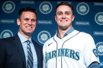 Seattle Mariners general manager Jerry Dipoto, left, and new first baseman Evan White pose for photographs with White's new jersey after a news conference at T-Mobile Park Monday, Nov. 25, 2019 in Seattle. (Andy Bao/The Seattle Times via AP)