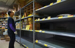 A worker checks empty shelf of rice at a supermarket in Hong Kong, Thursday, Feb. 6, 2020. Ten more people were sickened with a new virus aboard one of two quarantined cruise ships with some 5,400 passengers and crew aboard, health officials in Japan said Thursday, as China reported 73 more deaths and announced that the first group of patients were expected to start taking a new antiviral drug. (AP Photo/Vincent Yu)
