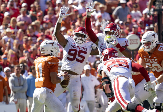 Texas quarterback Casey Thompson (11) has nowhere to go with the ball as Oklahoma defenders Isaiah Thomas (95), Nik Bonitto (11) and Danny Stutsman (28) close in during the second half of an NCAA college football game at the Cotton Bowl, Saturday, Oct. 9, 2021, in Dallas. Thompson was sacked on the play. (AP Photo/Jeffrey McWhorter)
