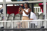 FILE - Olympic gymnast Simone Biles takes photos with her phone as she watches the Houston Texans practice at NFL football training camp in Houston, Friday, Aug. 6, 2021. Biles is at peace with her decision to opt out of several competitions at the Tokyo Olympics to focus on her mental health. The seven-time Olympic medalist is happy to spread the importance of putting the person ahead of the athlete, one of the themes of her fall exhibition tour that will feature four other members of the 2021 Olympic gymnastics team(Brett Coomer/Houston Chronicle via AP, File)