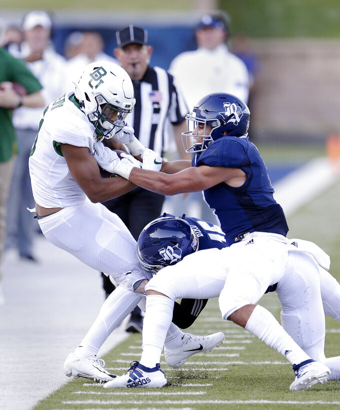 Baylor wide receiver R.J. Sneed, left, is tackled by Rice defensive end Cameron Valentine, middle, and defensive back Prudy Calderon, right, during the first half of an NCAA college football game Saturday, Sept. 21, 2019, in Houston. (AP Photo/Michael Wyke)