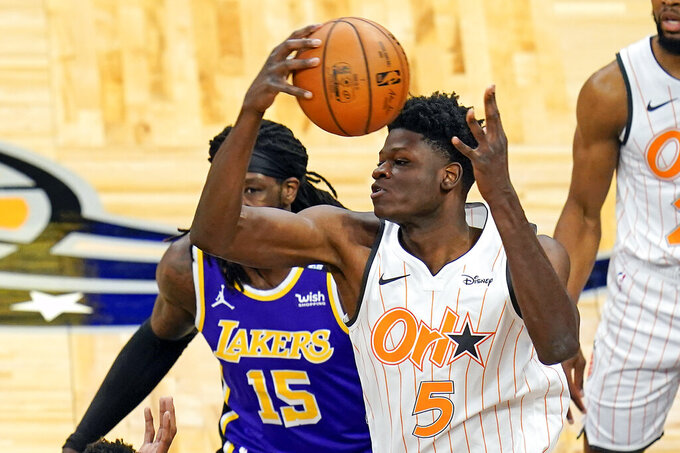 Orlando Magic center Mo Bamba (5) collects a rebound in front of Los Angeles Lakers center Montrezl Harrell (15) during the first half of an NBA basketball game, Monday, April 26, 2021, in Orlando, Fla. (AP Photo/John Raoux)