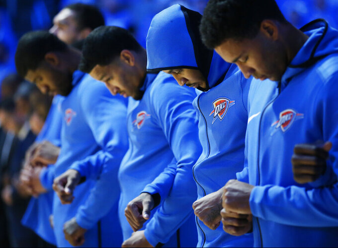 FILE - In this Oct. 19, 2017, file photo, from left, Paul George, Andre Roberson, Carmelo Anthony and Josh Heustis link arms during the playing of the national anthem before an NBA basketball game against the New York Knicks in Oklahoma City. Dallas Mavericks coach Rick Carlisle isn't sure what to expect from players during the national anthem when the NBA season resumes in empty arenas late this month in Florida. (AP Photo/Sue Ogrocki, File)