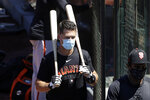 FILE - In this Sunday, July 5, 2020, file photo, San Francisco Giants' Buster Posey carries his bats during baseball practice in San Francisco. Posey is the latest big-name player to skip this season because of concerns over the coronavirus pandemic. (AP Photo/Jeff Chiu, File)