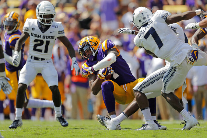 LSU wide receiver Ja'Marr Chase (1) pulls in a pass between Utah State cornerback DJ Williams (7) and cornerback Andre Grayson (21) in the first half of an NCAA college football game in Baton Rouge, La., Saturday, Oct. 5, 2019. (AP Photo/Gerald Herbert)