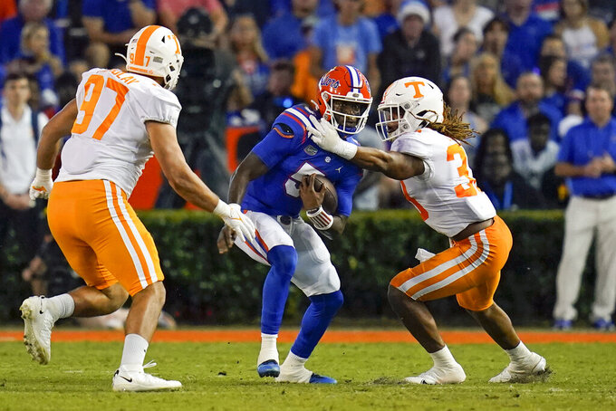 Florida quarterback Emory Jones, center, tries to run between Tennessee defensive lineman Caleb Tremblay (97) and linebacker Jeremy Banks, right, during the first half of an NCAA college football game, Saturday, Sept. 25, 2021, in Gainesville, Fla. (AP Photo/John Raoux)
