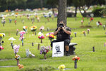 A mourner adjusts his mask as he waits for George Floyd's funeral procession at Houston Memorial Gardens cemetery in Pearland, Texas. (AP Photo/Eric Gay)