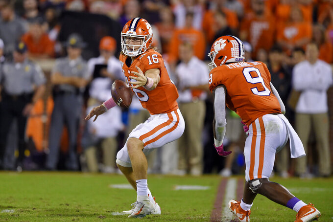 Clemson's Trevor Lawrence (16) grabs the ball in front of Travis Etienne after a bad snap during the first half of an NCAA college football game against Boston College, Saturday, Oct. 26, 2019, in Clemson, S.C. (AP Photo/Richard Shiro)