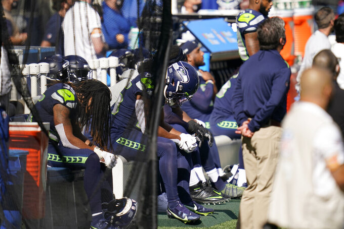 Seattle Seahawks players sit on a bench during the national anthem beore an NFL football game against the Dallas Cowboys, Sunday, Sept. 27, 2020, in Seattle. (AP Photo/Elaine Thompson)