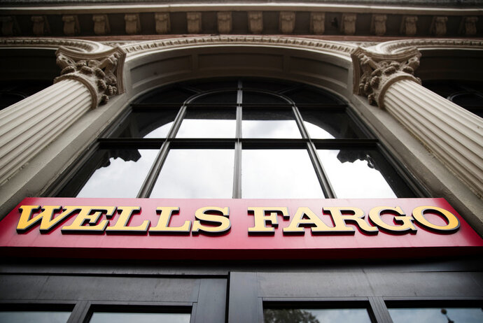 FILE- This Friday, Aug. 11, 2017, file photo shows a sign at a Wells Fargo bank location in Philadelphia. Wells Fargo reports earnings Friday, April 13, 2018. (AP Photo/Matt Rourke, File)