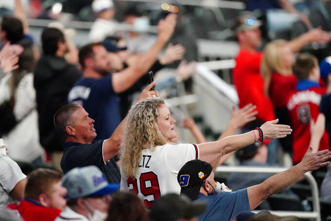 FILE - In this  Saturday, April 10, 2021 file photo, Atlanta Braves fans do the Tomahawk Chop during a baseball game against the Philadelphia Phillies in Atlanta. As the World Series shifts to Atlanta, some TV viewers may be offended to see Braves fans still chopping and chanting. After teams in the NFL and Major League Baseball have dropped names viewed as offensive to Native Americans the last two years, the Braves chop on. The tomahawk chop has the support of baseball commissioner Rob Manfred. (AP Photo/John Bazemore, File)