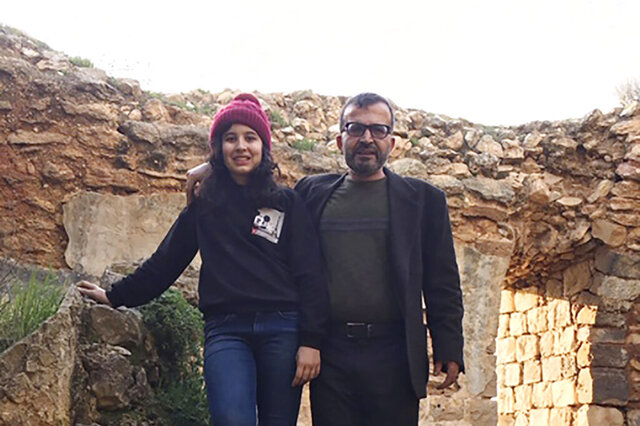 In this March 12, 2020 photo made available by Reem Mousa, Ismail Mousa and his daughter Anisa of Selbyville, Delaware, pose for a photograph while sightseeing near the Palestinian village of Qaryout in the West Bank. Mousa and his daughter found themselves stranded and separated from each other after their travels plans and efforts to return home were thwarted because of the coronavirus pandemic. (Reem Mousa via AP)