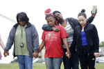A group prays near a makeshift memorial at the spot where missing children, Miracle Crook, 3, and Tony Crook, 2, walked down to Mingo Creek at the Shoreline Apartments Wednesday, May 27, 2020, in Tulsa, Okla. Christal McLemore, second left, is comforted by Takenna Triplett during the prayer. McLemore's grandaughter is the oldest sibling of the Crooks. (Mike Simons/Tulsa World via AP)