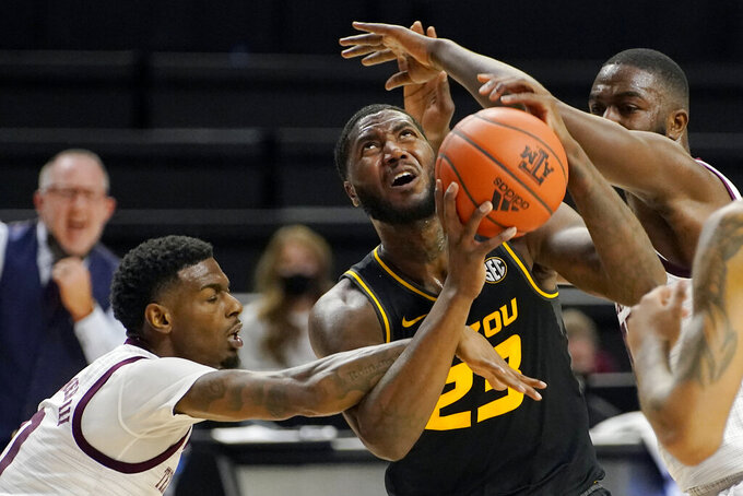 Missouri forward Jeremiah Tilmon (23) is fouled by Texas A&M guard Jay Jay Chandler (0) trying to shoot a basket during the first half of an NCAA college basketball game Saturday, Jan. 16, 2021, in College Station, Texas. (AP Photo/Sam Craft)