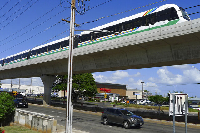 FILE - In this May 30, 2017, file photo, a rail car tops an elevated rail line in Waipahu, Hawaii. Honolulu is building one of the nation's most expensive rail lines to address some of the nation's worst traffic but tax revenue declines during the pandemic and spiraling costs mean it doesn't currently have enough money to finish the 20-mile route as planned. (AP Photo/Cathy Bussewitz, File)