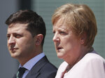 German Chancellor Angela Merkel welcomes Ukraine's President Volodymyr Zelenskiy with military honors for a meeting at the chancellery in Berlin, Germany, Tuesday, June 18, 2019. (AP Photo/Michael Sohn)