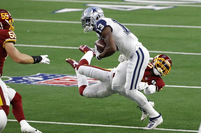 Dallas Cowboys wide receiver Michael Gallup (13) attempts to escape the grasp of Washington Football Team cornerback Jimmy Moreland, rear, in the first half of an NFL football game in Arlington, Texas, Thursday, Nov. 26, 2020. (AP Photo/Roger Steinman)