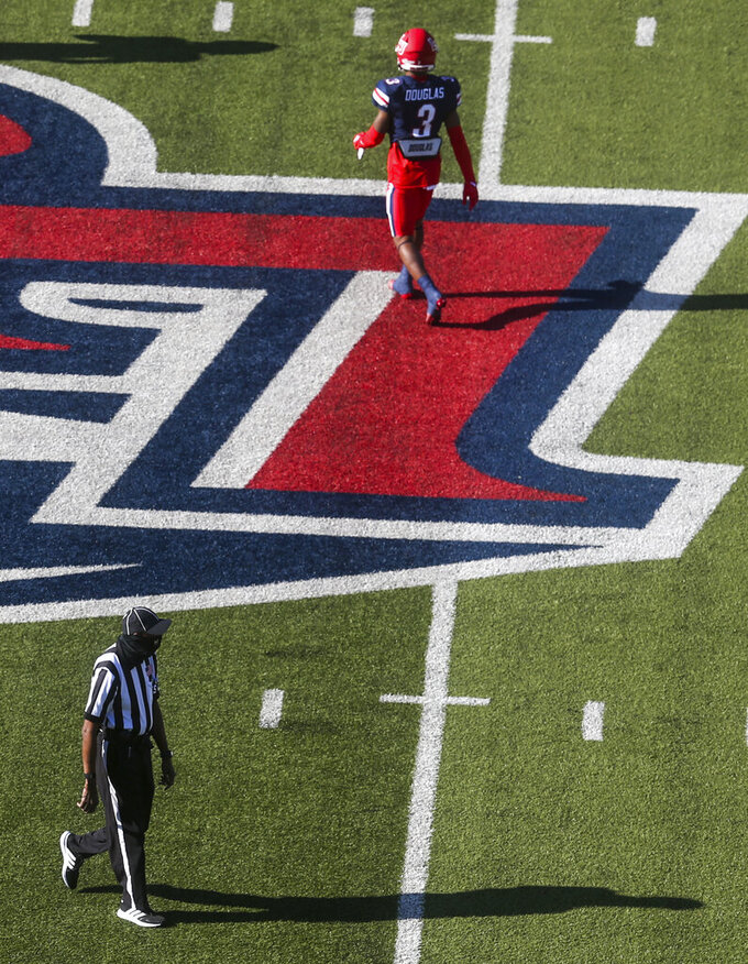 Liberty wide receiver Demario Douglas (3) warms up as a referee walks the field before a NCAA college football game between Massachusetts and Liberty on Friday, Nov. 27, 2020, at Williams Stadium in Lynchburg, Va. (AP Photo/Shaban Athuman)