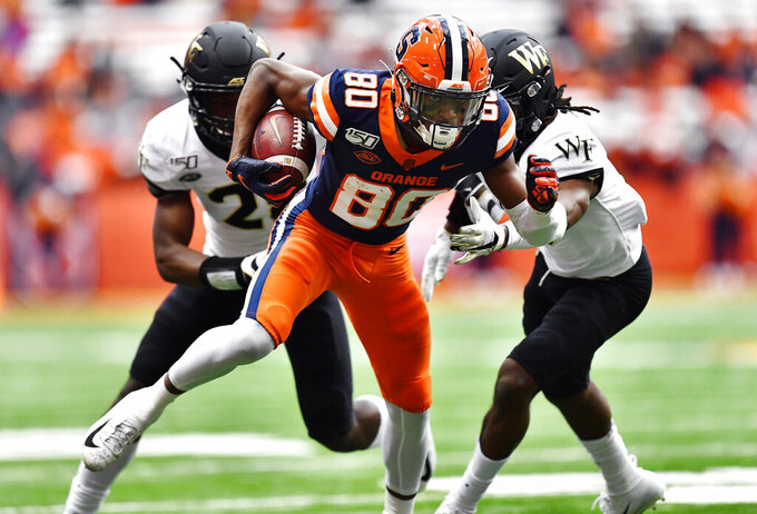 Syracuse wide receiver Taj Harris (80) eludes Wake Forest defensive back Zion Keith, left, and defensive back Ja'Sir Taylor after a catch during the first half of an NCAA college football game in Syracuse, N.Y., Saturday, Nov. 30, 2019. (AP Photo/Adrian Kraus)