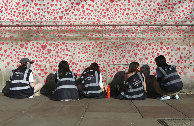 People draw hearts on the National Covid Memorial Wall, which is being painted in memory of the more than 145,000 people who have died in the UK from coronavirus, on the Embankment in central London, Tuesday, March 30, 2021. (Luciana Guerra/PA via AP)