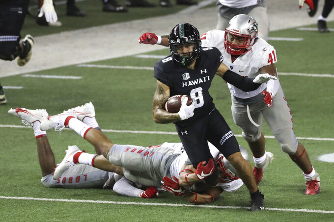 New Mexico linebacker Dion Hunter (41) tries to pull down Hawaii wide receiver Rico Bussey (8) during the second quarter of an NCAA college football game Saturday, Nov. 7, 2020, in Honolulu. (AP Photo/Marco Garcia)
