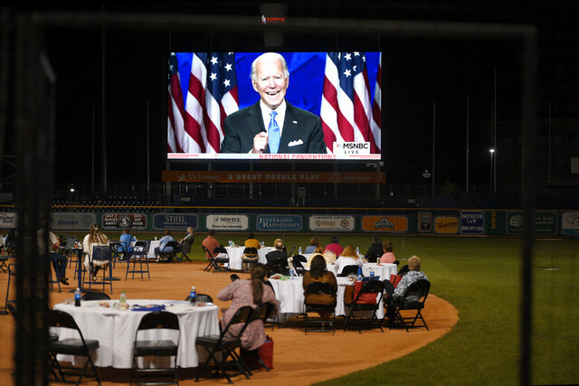 People watch Democratic presidential candidate and former Vice President Joe Biden speak at a watch party for the Democratic National Convention at Dunkin' Donuts Park, home of the minor league baseball team the Hartford Yard Goats, Thursday, Aug. 20, 2020, in Hartford, Conn. (AP Photo/Jessica Hill)