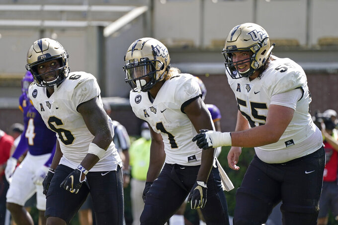 Central Florida wide receiver Marlon Williams (6), wide receiver Jaylon Robinson (1) and offensive lineman Matthew Lee (55) react following Robinson's touchdown against East Carolina during the second half of an NCAA college football game in Greenville, N.C., Saturday, Sept. 26, 2020. (AP Photo/Gerry Broome)