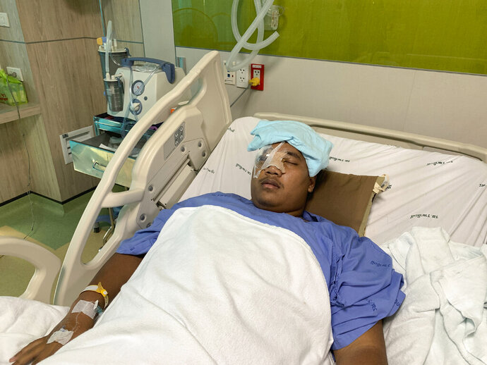 Pro-democracy leader Sirawith Seritiwat is hospitalized following last week's attack in Bangkok, Thailand, Wednesday, July 3, 2019. Rights groups are urging local authorities to investigate attacks against pro-democracy activists after one was beaten and left unconscious on a sidewalk last week. (AP Photo/Weerachai Fendi)