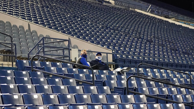 Two people sits in the stands during the first half of an NCAA college football game between BYU and Troy on Saturday, Sept. 26, 2020, in Provo, Utah. (AP Photo/Rick Bowmer, Pool)