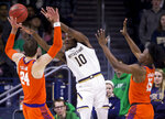 Notre Dame's T.J. Gibbs Jr. (10) passes around Clemson's David Skara (24) and John Newman III (15) during the first half of an NCAA college basketball game Wednesday, March 6, 2019, in South Bend, Ind. (AP Photo/Robert Franklin)