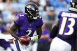 Baltimore Ravens quarterback Tyler Huntley looks to hand off against the Carolina Panthers during the first half of a preseason NFL football game Saturday, Aug. 21, 2021, in Charlotte, N.C. (AP Photo/Jacob Kupferman)