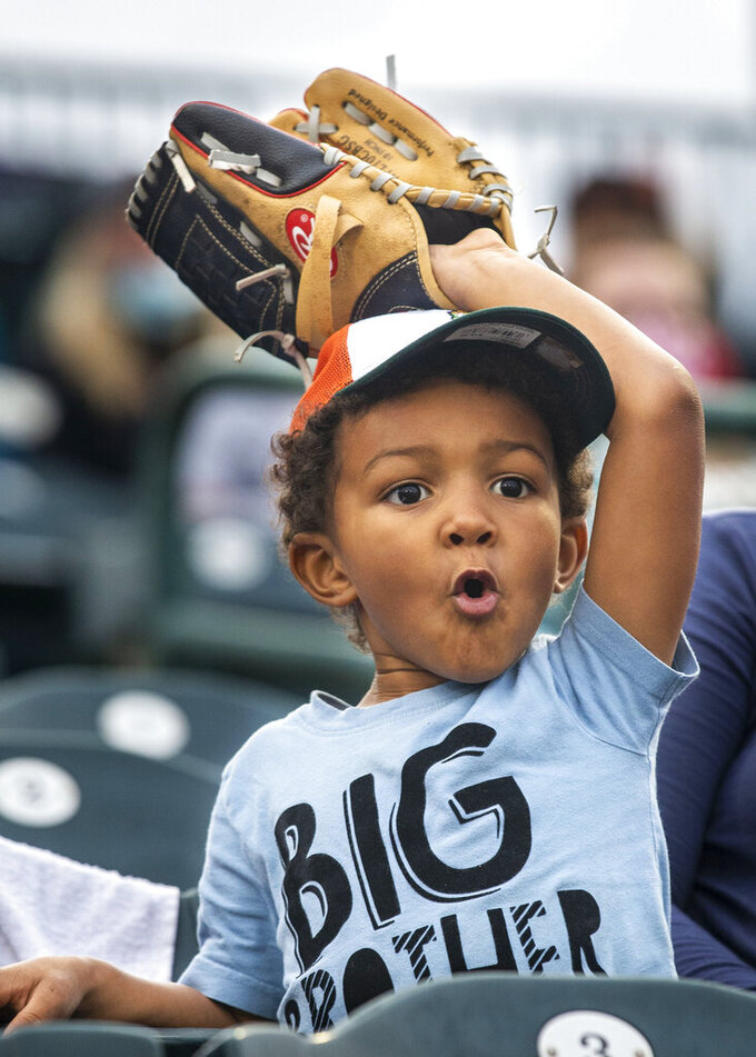 Quincy Lofton, 3, reacts to a base hit during a minor league baseball game between the Greensboro Grasshoppers and Hickory Crawdads in Greensboro, N.C., Tuesday, May 4, 2021. Minor league teams across the country opened their seasons Tuesday, returning baseball to communities denied the old national pastime during the coronavirus pandemic. (WoodyMarshall/News & Record via AP)