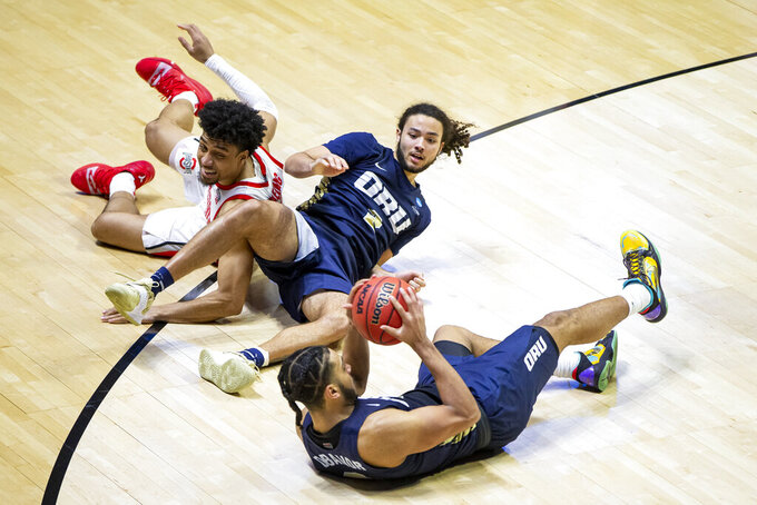 Oral Roberts' Kevin Obanor, bottom, looks to pass after recovering the ball during a scrum involving teammate Kareem Thompson, center, and Ohio State's Justice Sueing during the second half of a first-round game in the NCAA men's college basketball tournament, Friday, March 19, 2021, at Mackey Arena in West Lafayette, Ind. Oral Roberts won in overtime. (AP Photo/Robert Franklin)