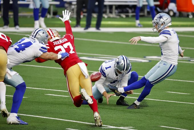 Dallas Cowboys place kicker Greg Zuerlein (2) kicks a 48-yard field goal as San Francisco 49ers cornerback Dontae Johnson (27) rushes on the play in the first half of an NFL football game in Arlington, Texas, Sunday, Dec. 20, 2020. Cowboys Hunter Niswander (1) holds on the kick. (AP Photo/Michael Ainsworth)