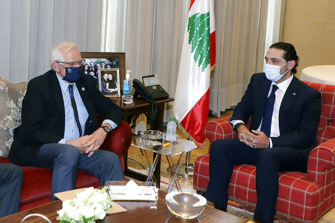 In this photo released by Lebanese government, Lebanese Prime Minister-Designate Saad Hariri, right, meets with European Union foreign policy chief Josep Borrell, in Beirut, Lebanon, Saturday, June. 19, 2021. Borrell berated Lebanese politicians for delays in forming a new Cabinet, warning the union could impose sanctions on those behind the political stalemate in the crisis-hit country. (Dalati Nohra/Lebanese Official Government via AP)