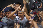 """FILE - In this Sept. 3, 2018 file photo, Reuters journalist Kyaw Soe Oo, center, talks to journalists while he is escorted by police as he leaves the court in Yangon, Myanmar. More than a dozen global news organizations including The Associated Press have formed a coalition to spotlight the world's most threatened journalists. Member editors and publishers of the One Free Press Coalition will publish across platforms each month a """"10 Most Urgent"""" list of journalists whose press freedoms are being abused. (AP Photo/Thein Zaw)"""